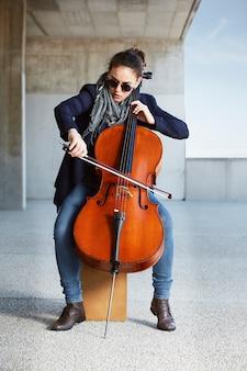 Schönes mädchen spielt das cello mit leidenschaft in einer konkreten umgebung