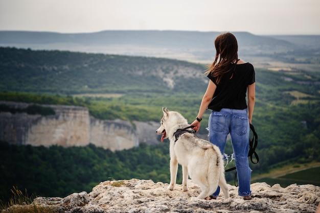 Schönes mädchen spielt mit einem hund, grauer und weißer husky, in den bergen bei sonnenuntergang. inderin und ihr wolf