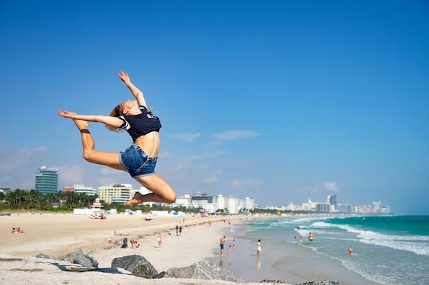 Schönes mädchen springen mit south beach, miami beach. florida. konzept von glück und freiheit.