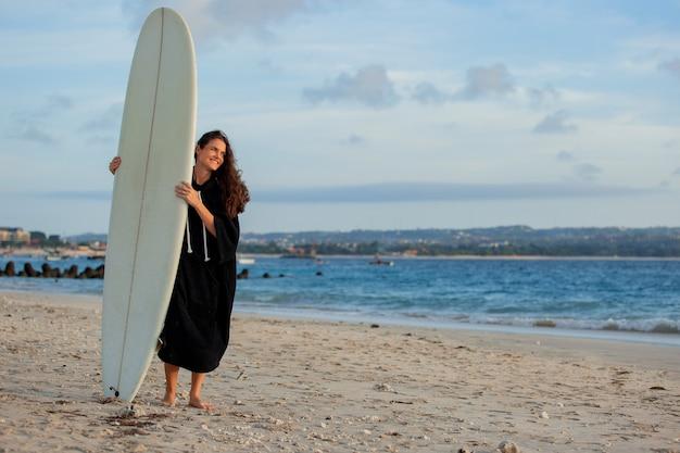 Schönes mädchen steht am strand mit einem surfbrett.
