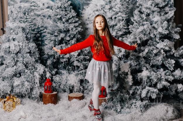 Schönes mädchen steht auf dem boden nahe bäumen der weißen weihnacht