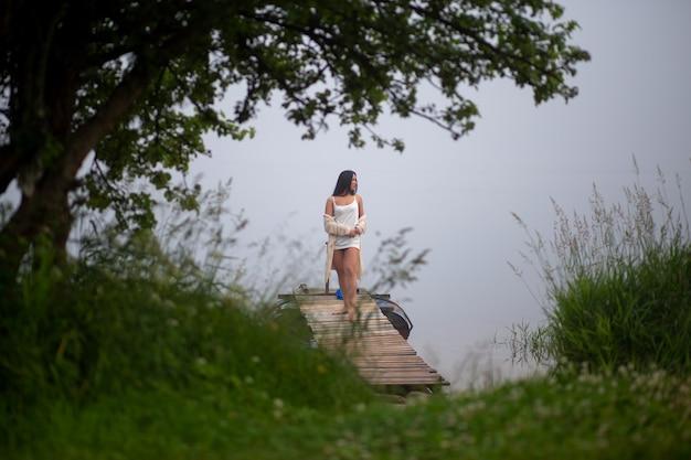 Schönes mädchen steht auf dem pier am fluss