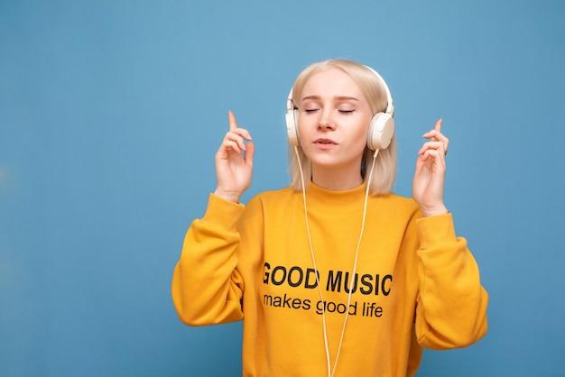 Schönes mädchen steht auf einem blauen hintergrund in den kopfhörern und hört musik mit ihren geschlossenen augen, die orange freizeitkleidung tragen