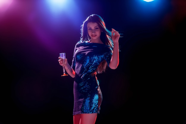 Schönes mädchen tanzt auf der party champagner trinkend