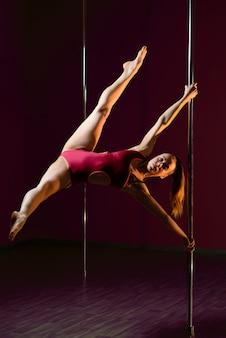 Schönes mädchen tanzt auf einem pylon.