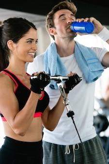 Schönes mädchen trainiert im fitnessstudio mit personal trainer