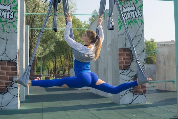 Schönes mädchen trainiert in einer hängematte im freien.