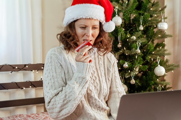 Schönes mädchen trifft eine schwierige wahl, wenn sie geschenke online für weihnachten kaufen