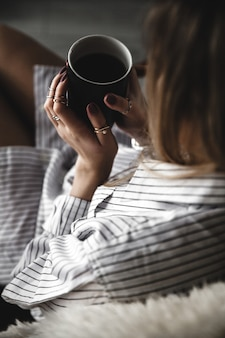 Schönes mädchen trinkt kaffee mit einer schwarzen tasse im hemd, mode, essen