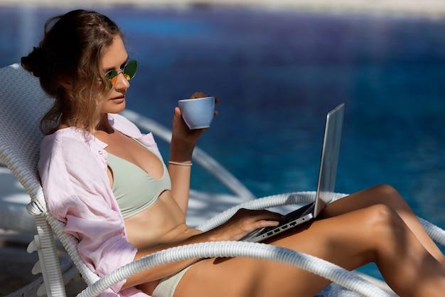 Schönes mädchen trinkt kaffee nahe dem pool