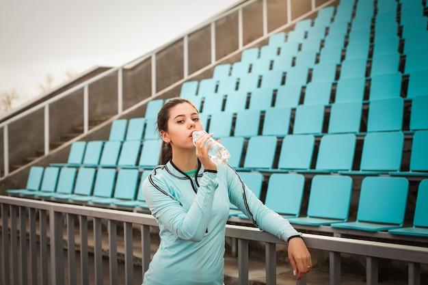 Schönes mädchen trinkt wasser von einer flasche nach sporttraining