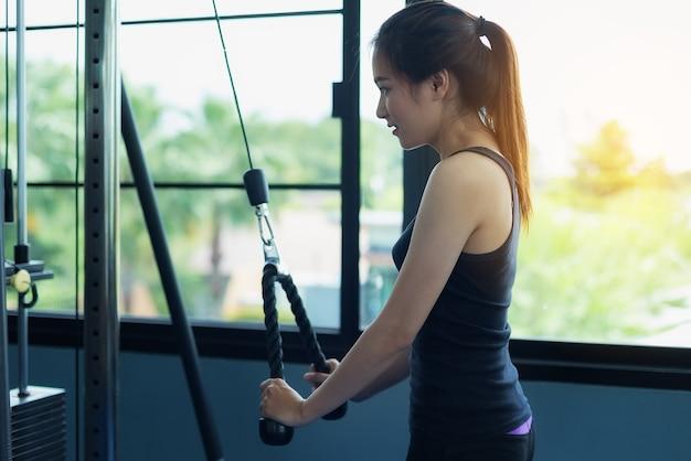 Schönes mädchen übt, indem es das seil zieht, um die muskeln in der allgemeinen turnhalle zu verstärken