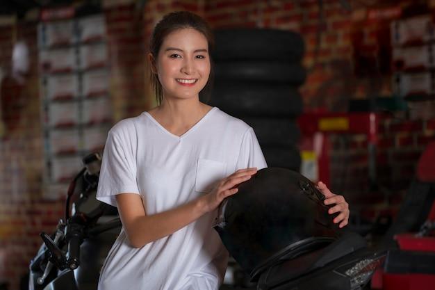 Schönes mädchen und ein motorradsturzhelm mit motorrad