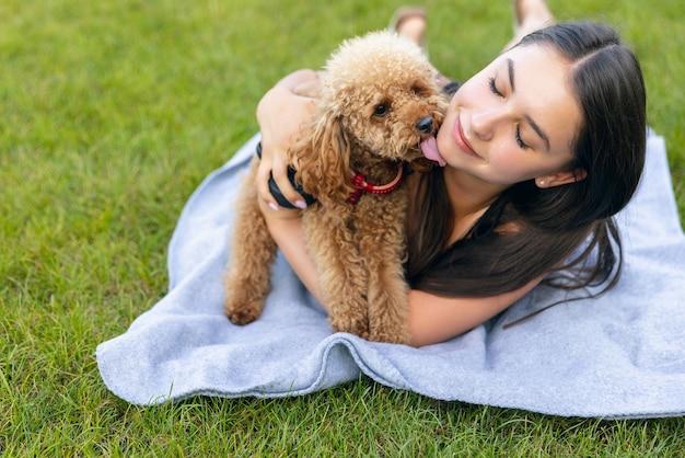 Schönes mädchen und ihr kleiner goldener pudelhund, der draußen im öffentlichen park spazieren geht