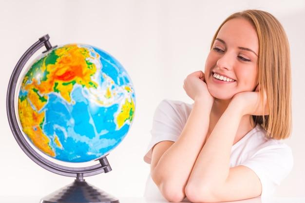 Schönes mädchen und schaut auf den globus.
