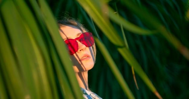 Schönes mädchen unter den blättern des exotischen baumes auf einem sonnenuntergang