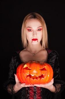Schönes mädchen verkleidet wie ein vampir, der einen kürbis für halloween über schwarzem hintergrund hält.