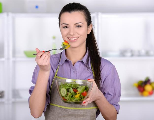 Schönes mädchen versuchen einen gesunden und leckeren salat.