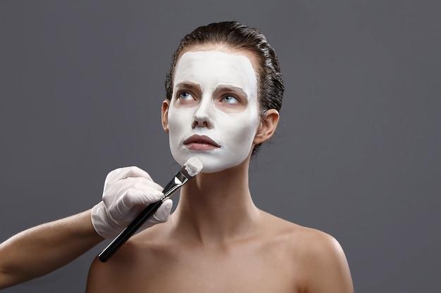 Schönes mädchen wird eine weiße kosmetische maske aus schwarzen punkten aufgetragen