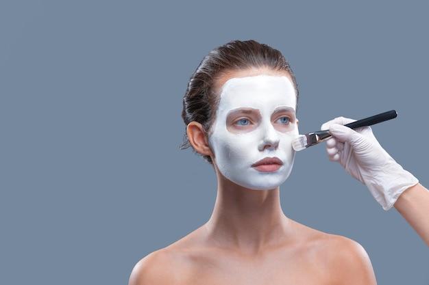 Schönes mädchen wird eine weiße kosmetische maske von schwarzen punkten isolatstudio angewendet
