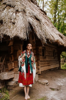 Schönes mädchen wirft auf den höfen nahe dem haus in einem traditionellen ukrainischen kleid auf