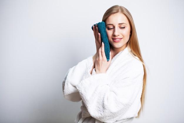 Schönes mädchen wischt ihr gesicht mit einem handtuch zu hause
