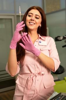 Schönes mädchen zahnarzt hält eine spritze in der hand. lächeln und in die kamera schauen. anästhesie und injektionen in der zahnmedizin.