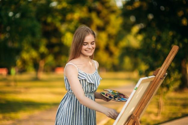 Schönes mädchen zeichnet ein bild im park unter verwendung einer palette mit farben und einem spatel. staffelei und leinwand mit einem bild.