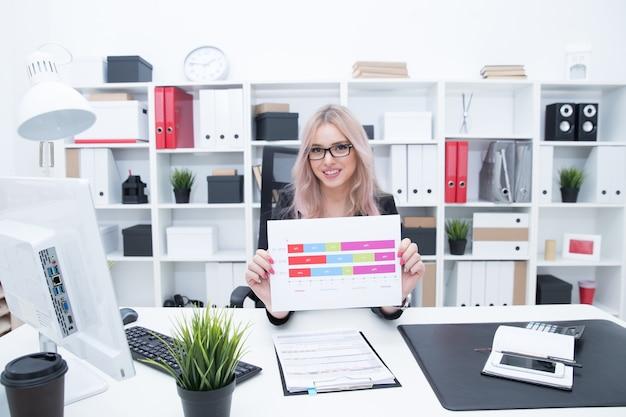Schönes mädchen zeigt arbeitspläne auf dem hintergrund des büros