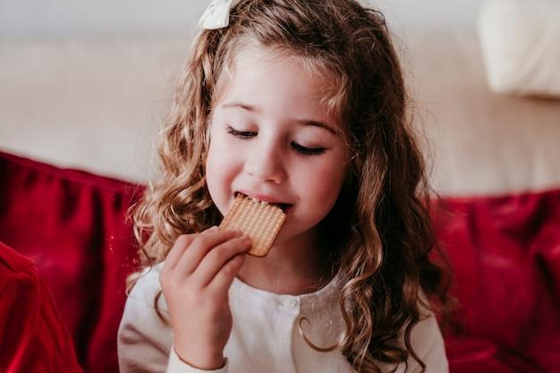 Schönes mädchen zu hause, das einen köstlichen snack isst