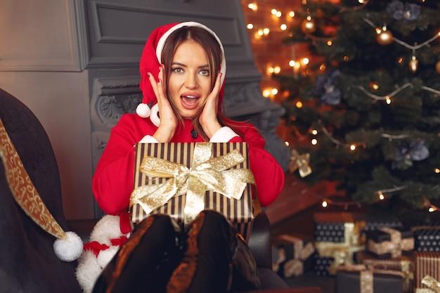 Schönes mädchen zu hause im kostüm eines weihnachtsmanns