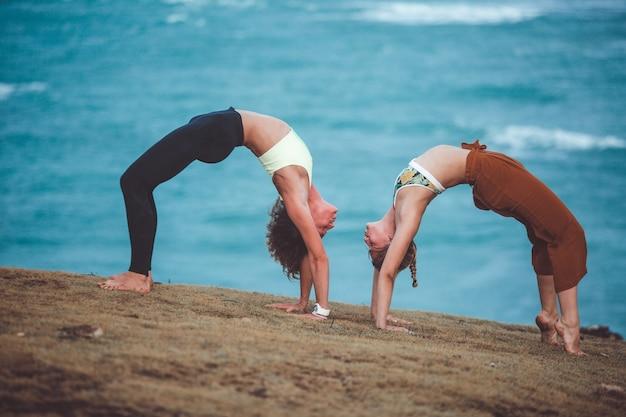 Schönes mädchen zwei, das yoga tut