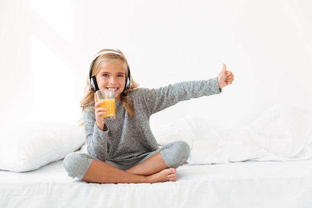 Schönes mädchenkind in den kopfhörern, die glas orangensaft halten, zeigen daumen hoch geste, während im bett sitzen