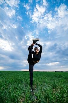 Schönes mädchenmodell auf grünem gras tun yoga. eine schöne brünette auf einem grünen rasen führt akrobatische elemente durch. flexible turnerin in schwarz macht übungen