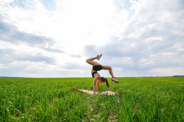 Schönes mädchenmodell auf grünem gras tun yoga. eine schöne junge frau auf einem grünen rasen führt akrobatische elemente durch. flexible turnerin in schwarz macht einen handstand im split