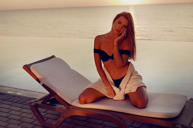 Schönes mädchenmodell, das auf einem sonnenbett nahe dem pool aufwirft