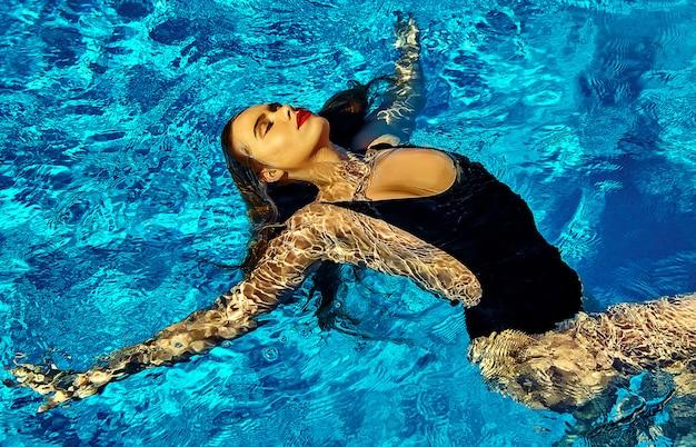 Schönes mädchenmodell mit dem dunklen haar in der schwarzen badebekleidung
