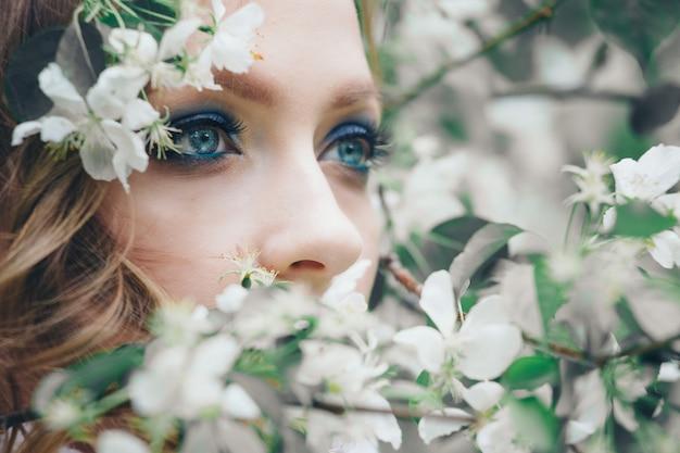 Schönes mädchenmodell mit hellem make-up unter weißen blumen. porträt einer frauennahaufnahme