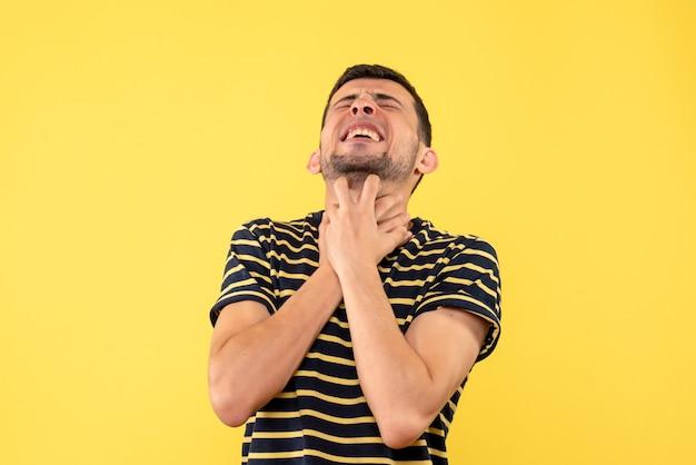 Schönes männchen der vorderansicht im gestreiften schwarzweiss-t-shirt, das kehle auf gelbem lokalisiertem hintergrund hält