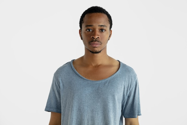 Schönes männliches halbes längenporträt lokalisiert auf weißer wand. junger emotionaler afroamerikanermann im blauen hemd. gesichtsausdruck, menschliche emotionen, anzeigenkonzept. stehend und schauend.