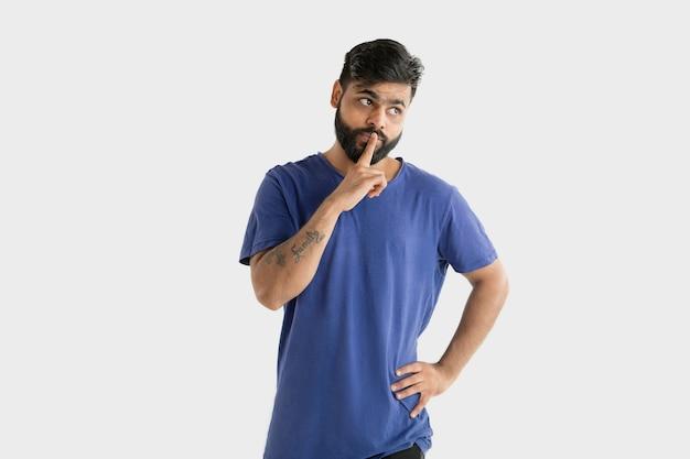 Schönes männliches halblanges porträt lokalisiert auf weißer wand. junger emotionaler hinduistischer mann im blauen hemd. gesichtsausdruck, menschliche emotionen, werbekonzept. nachdenken, ein geheimnis flüstern.