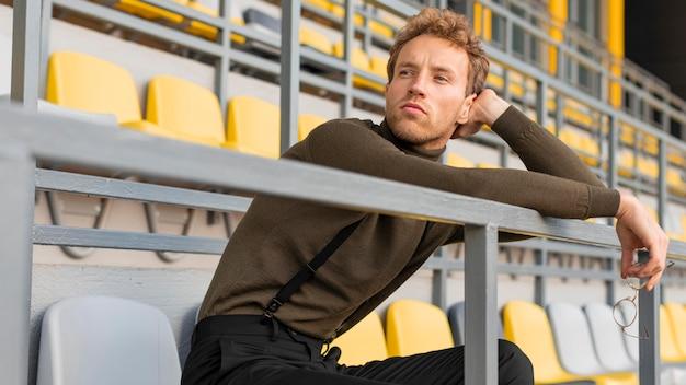 Schönes männliches modell, das in einem stadion sitzt
