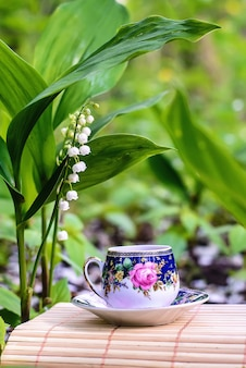 Schönes märchengrünbild mit einer kleinen tasse tee und maiglöckchen im garten im frühjahr