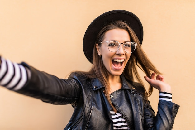 Schönes mode-mädchen in lederjacke, transparenter brille und schwarzem hut macht selfie isoliert auf hellgelber wand