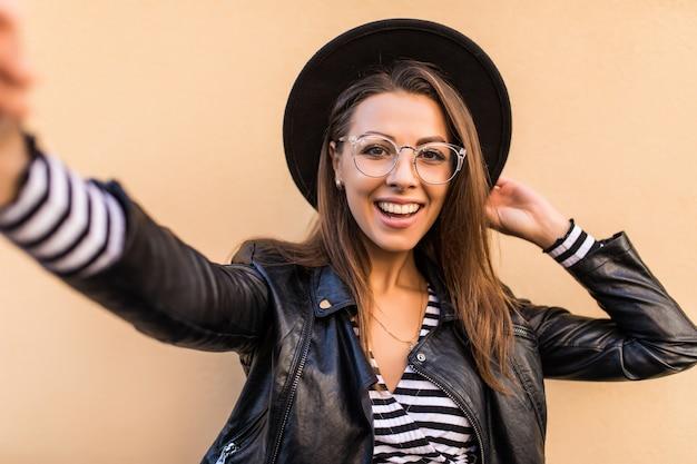 Schönes mode-mädchen in lederjacke und schwarzem hut macht selfie isoliert auf hellgelber wand