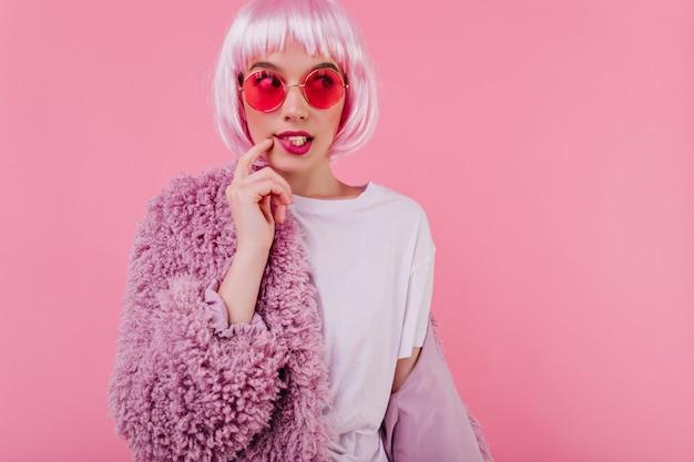 Schönes modeballenmädchen in der sonnenbrille, die auf rosa wand in pelzjacke aufwirft. jocund stilvolle dame in perücke, die spaß am fotoshooting hat