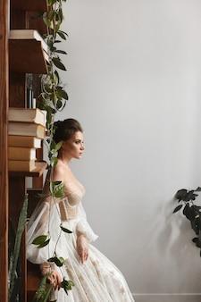 Schönes model-mädchen trägt ein vintage-hochzeitskleid mit langen ärmeln drinnen stilvolle junge braut i...