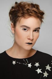 Schönes model mit haarsträhne, weißen augenpfeilen und schwarzem lippenstift.