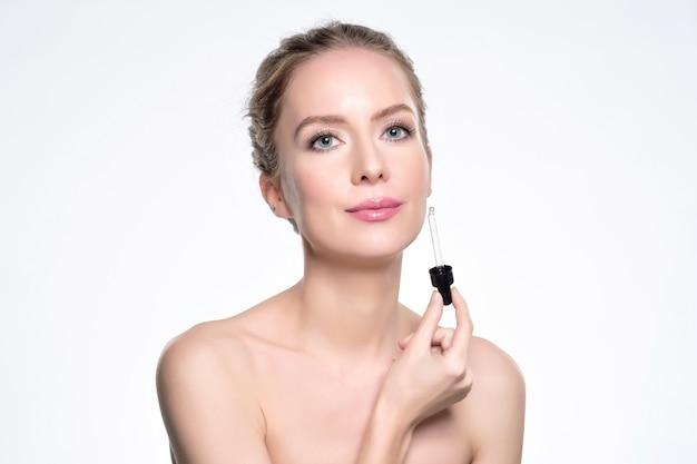 Schönes modell, das eine kosmetische hautserumbehandlung auf weiß anwendet