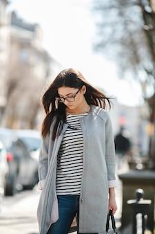 Schönes modell, das einen mantel trägt, spaziert in der europäischen stadt